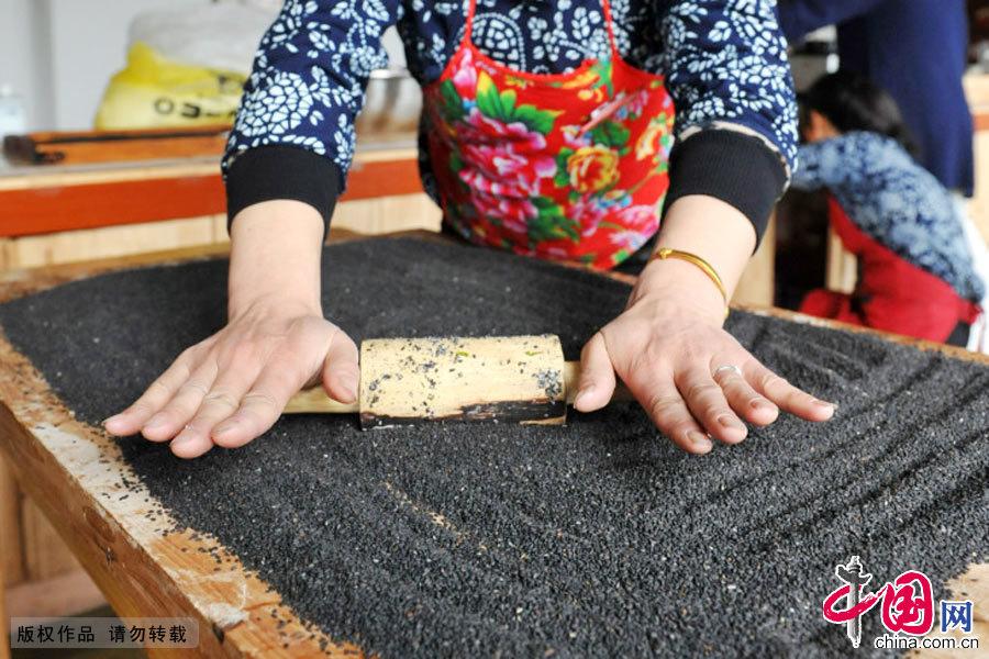 捏碎炒熟后的芝麻准备包入清明果内。