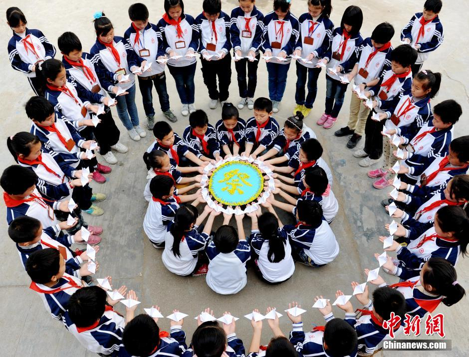 省婺源县太白镇中心小学寄宿学校的留守儿童,手持亲手制作的千纸鹤