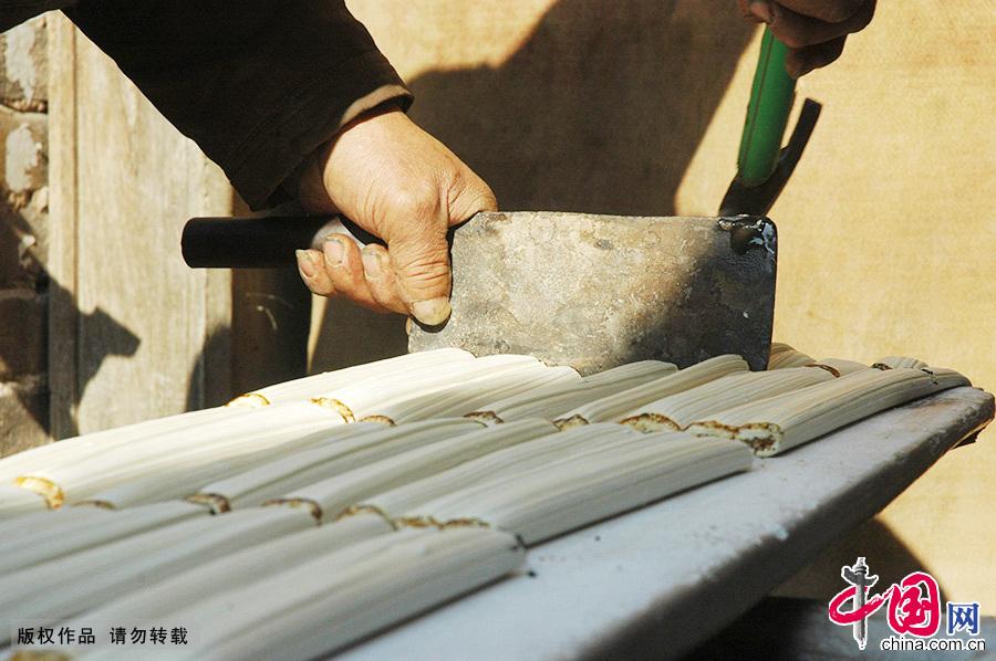 一名工匠在切制灶糖。