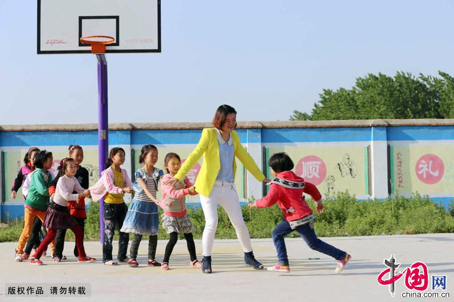 """課間活動時,楊巧老師和孩子們在一起玩""""老鷹捉小雞""""的遊戲。"""