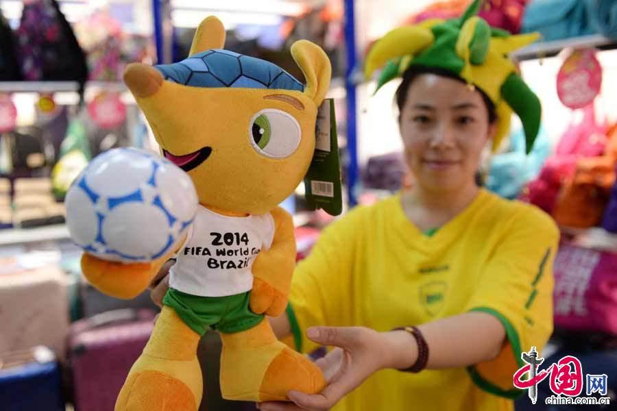 6月12日,一名店員在展示2014巴西世界盃的吉祥物福來哥。 中國網圖片庫 賴鑫琳攝影
