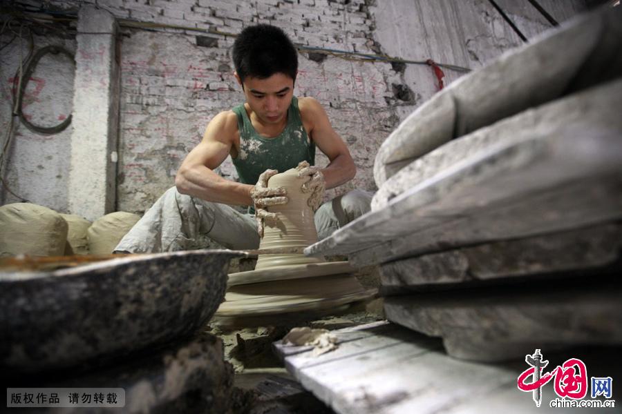 江西省景德镇艺术瓷厂内,1991年出生的吴望涛在拉坯。