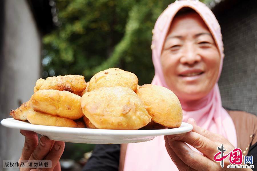 7月29日,一名清真餐馆员工展示自己制作的清真美食。