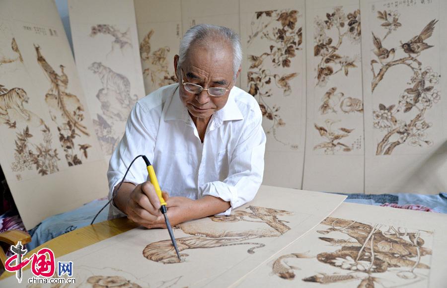 7月30日,河北省邯郸市邯郸县榆林村民间艺人张振芳正在用电烙铁作画。