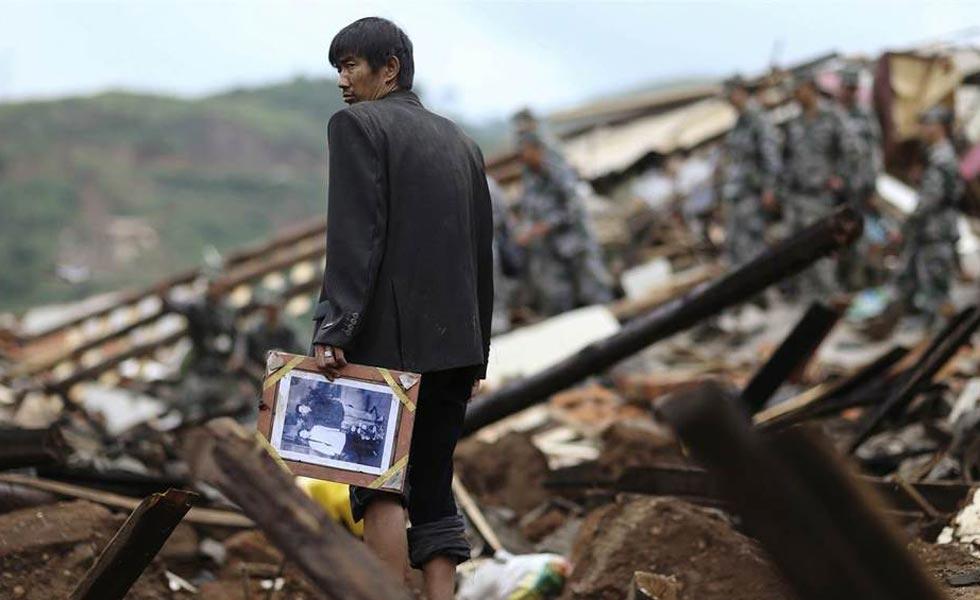 鲁甸地震灾区直击:废墟中拿着家人相片的男子