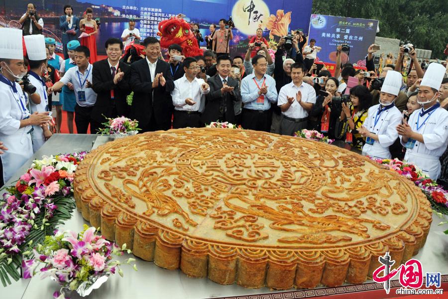 """2014年9月8日,甘肃省兰州市举办以""""浓情中秋 相约兰州""""为主题的共享中秋大型活动,""""世界最大的百合月饼""""在活动上亮相,数百名中外来宾共同分享""""世界最大的百合月饼""""。"""