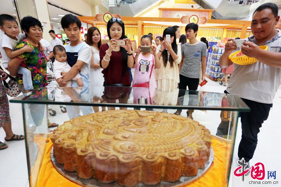 """2014年8月24日,许昌市民被一""""龙凤呈祥""""超级大月饼所吸引。"""