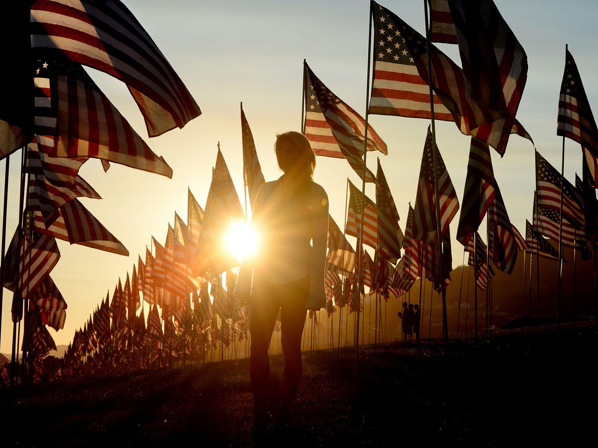 3000面美国国旗象征着3000名遇难者。一名来自女性站在夕阳下,缅怀逝者。