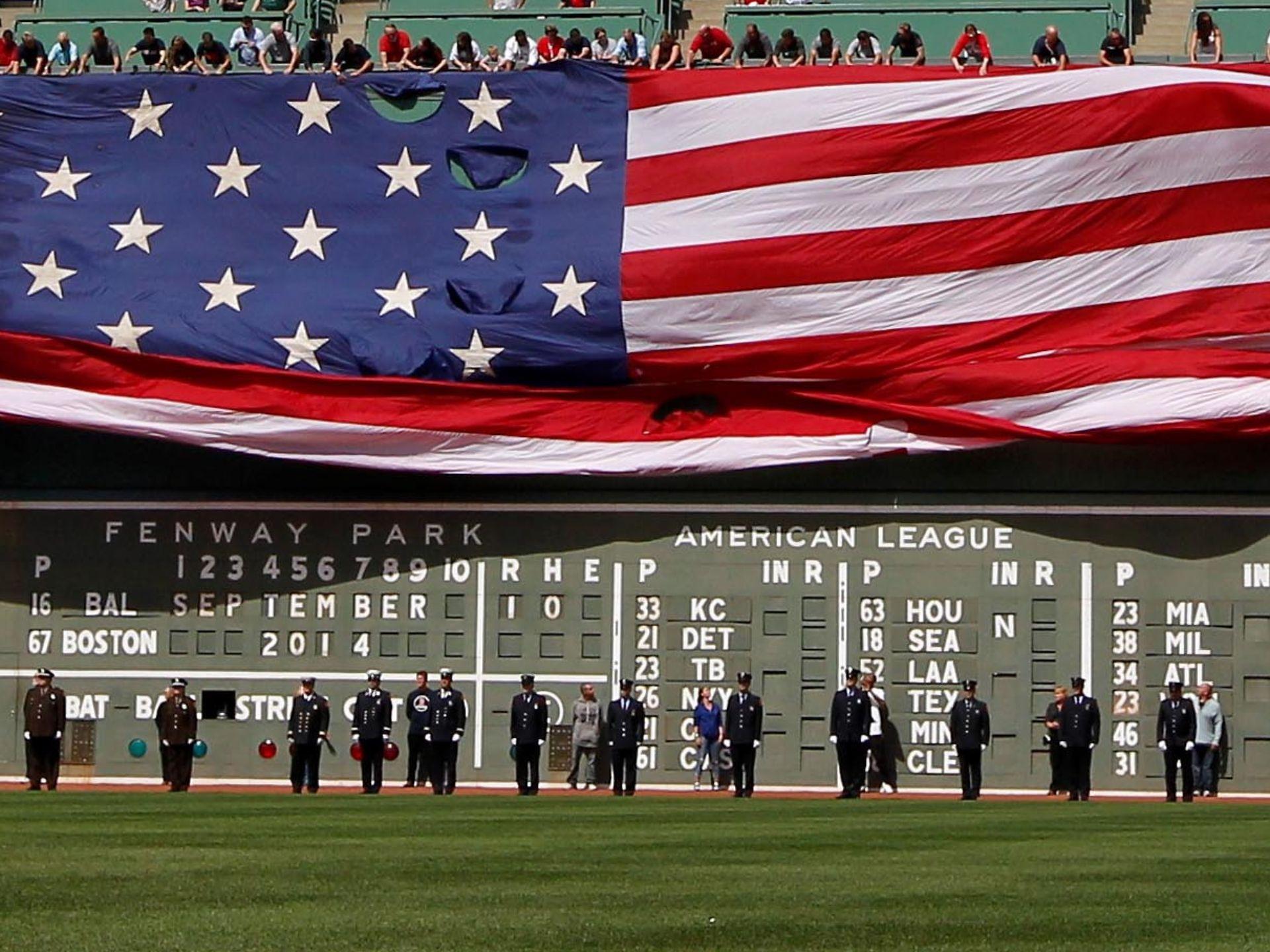 美国当地时间9月10日,在波士顿的芬威球场举行的一场棒球比赛开始前,球员和现场观众纪念911事件13周年。一面巨大的美国国旗悬挂在观众席上。