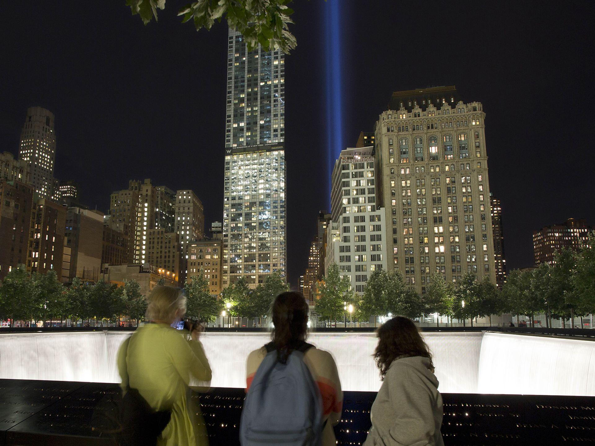 游客们在911国家纪念日观看在世贸大楼原址射向天空的灯光。