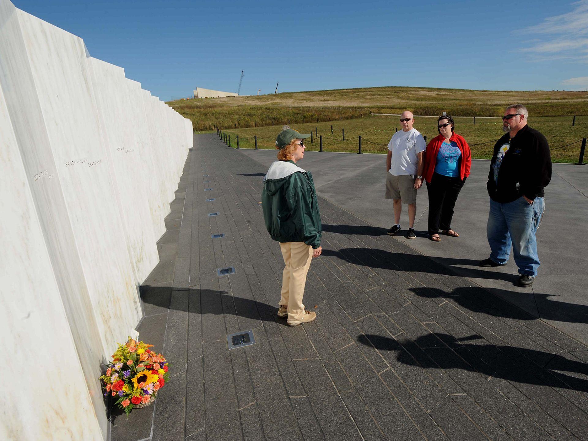 9月8日,志愿者朱迪·布兰特站在纪念墙前为参观者讲解。
