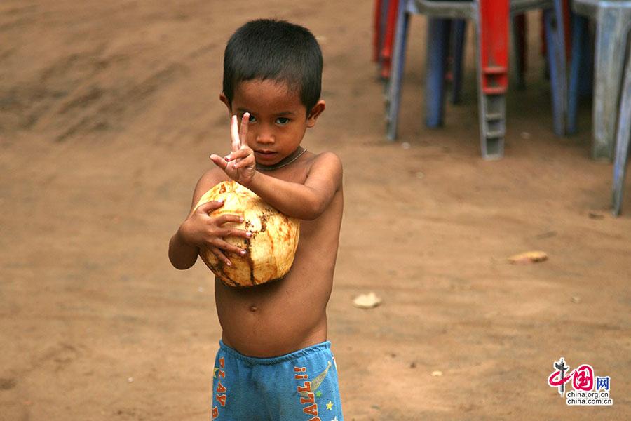 空中宫殿下面帮着母亲搬椰子卖的小男孩