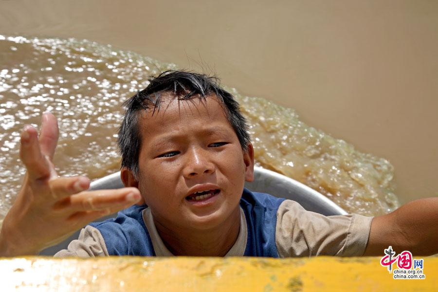 水上人家划着盆子来乞钱的小男孩
