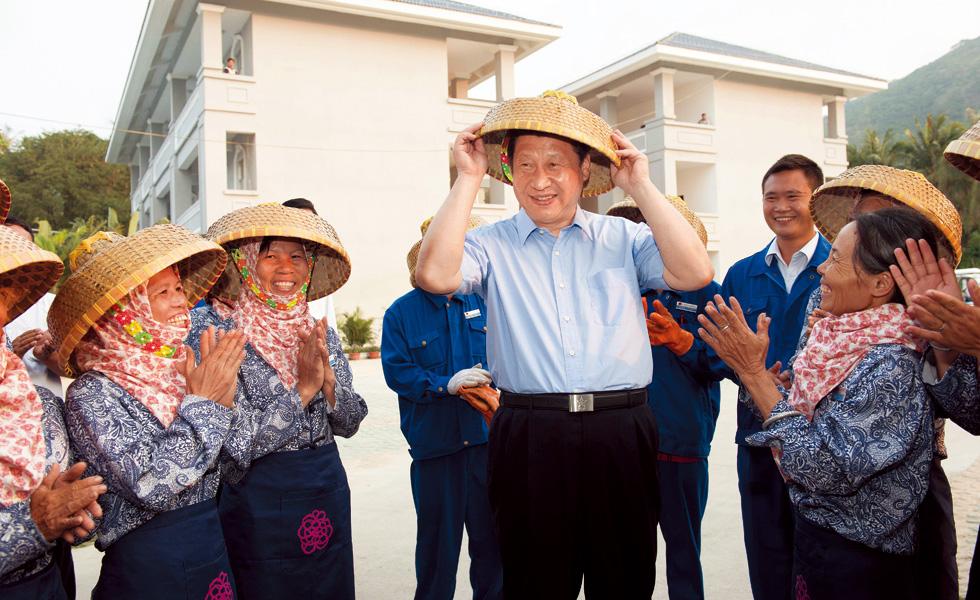 2013年4月9日,习近平在海南考察工作时,在亚龙湾兰德玫瑰风情产业园高兴地戴上黎族群众递上的斗笠。