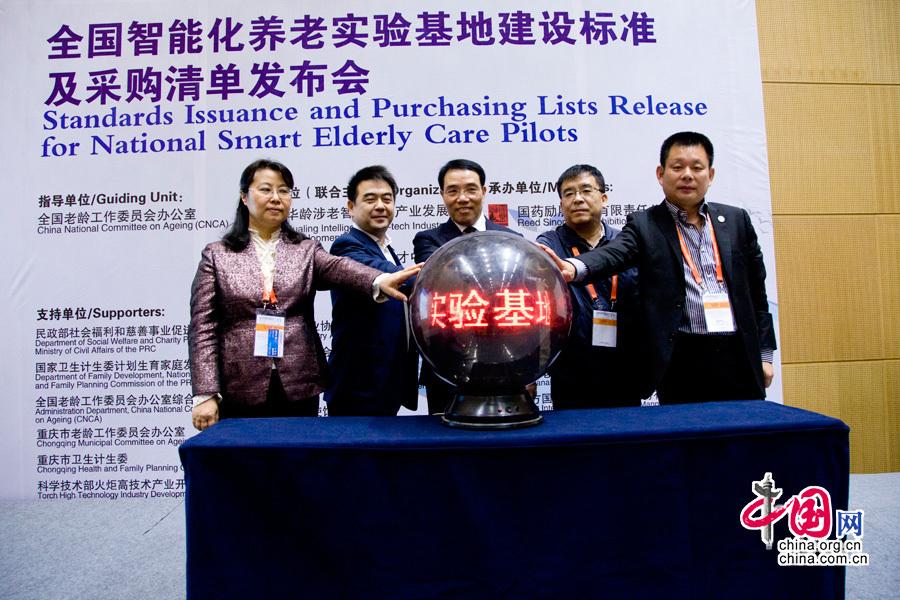 """2014年10月24日至25日,""""第三届全国智能化养老战略研讨会""""在山城重庆召开。图为与会嘉宾启动全国智能化养老实验基地建设标准。"""