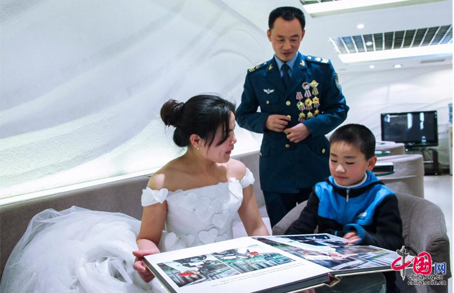 一家三口认真挑选拍摄照片。 摄影:谭超 自入伍以来,窦树军一直忙于工作,很少有时间陪在亲人身边,甚至连妻子想拍张婚纱照的愿望都迟迟不能兑现。适年底,他被评为第六届空军十大杰出青年,到北京领奖时,空军首长和机关听说这件事,专门派人把他妻儿从东北老家接到北京,帮助他们圆梦,于是便有了《迟拍11年的婚纱照》的美丽故事。(文/谭超) 【人物背景】 窦树军是沈空一名战机探伤技师,先后为9种型号、7500余架次飞机做过体检,发现裂纹故障 30多次,及时排除12起重大故障隐患。为国家挽回重大损失达数亿元,被誉为空军