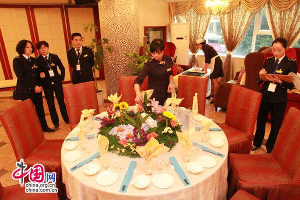 餐车服务员按照中餐宴席的餐桌布置标准进行摆台图片