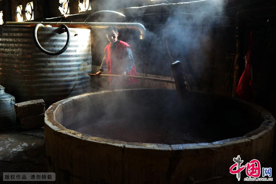 制酒师傅压紧蒸馏锅内原料。中国网图片库 周会/摄