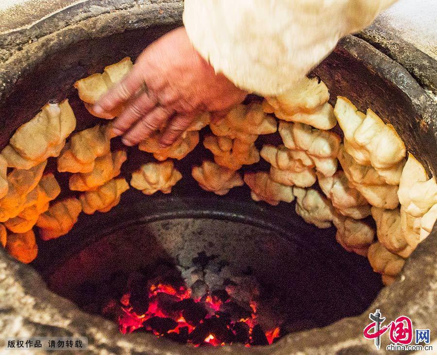 制作京江脐的时候,将加油的面粉揉成小团,呈馒头样,用刀轻轻切成六角形,然后贴进炉壁或推进烘炉,一会儿就飘出香味,铲下就可以吃了。中国网图片库 封疆江/摄