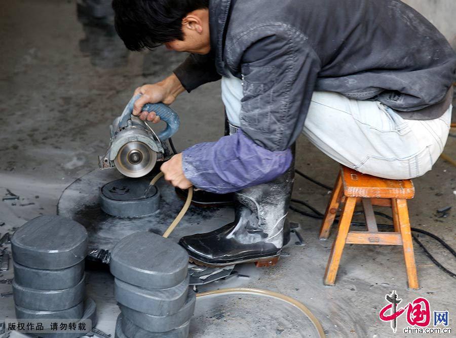 """歙砚制作技艺非常考究,从一块砚石石材到加工成歙砚成品,大致需要经过选料、制坯、设计、雕刻、磨光、上光、制盒和包装等十多道工序。图为一名民间工艺师正在对""""文房四宝""""中的歙砚进行制坯。中国网图片库 吴孙民/摄"""