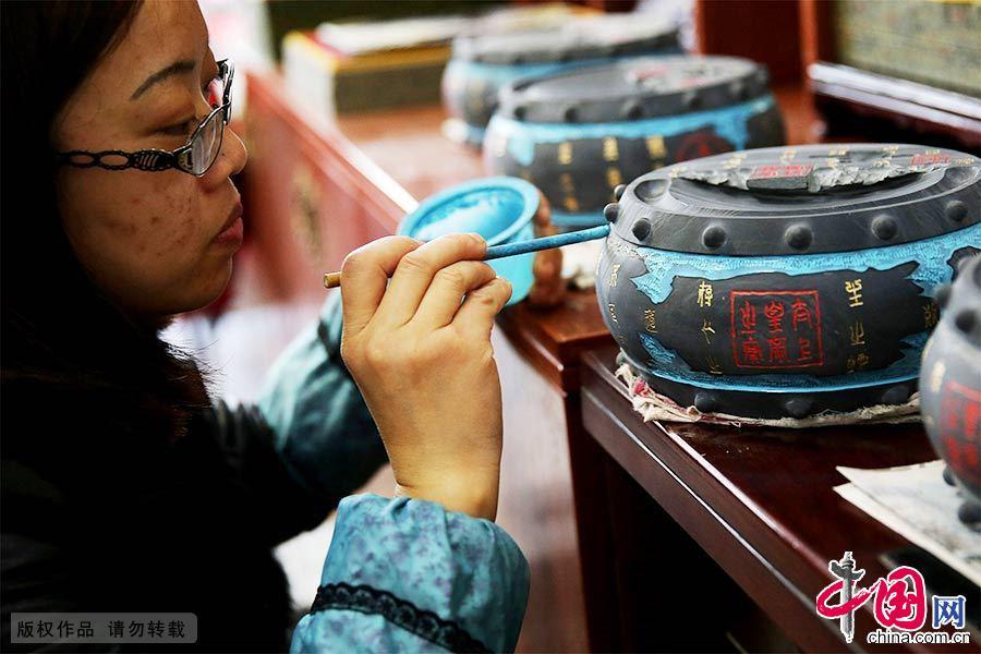 """一名工艺师正在对""""文房四宝""""中的歙砚进行描色。中国网图片库 吴孙民/摄"""
