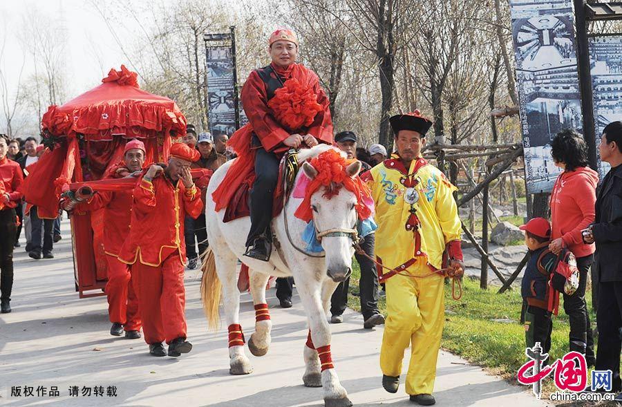 新郎在婚礼上骑着高头大马,迎接坐着花轿的新娘。中国网图片库 王明铭/摄