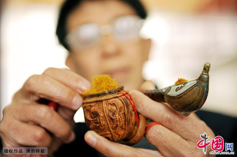 祝国根用自己十几年前创作的柚壳烟袋装烟丝。中国网图片库 卓忠伟/摄