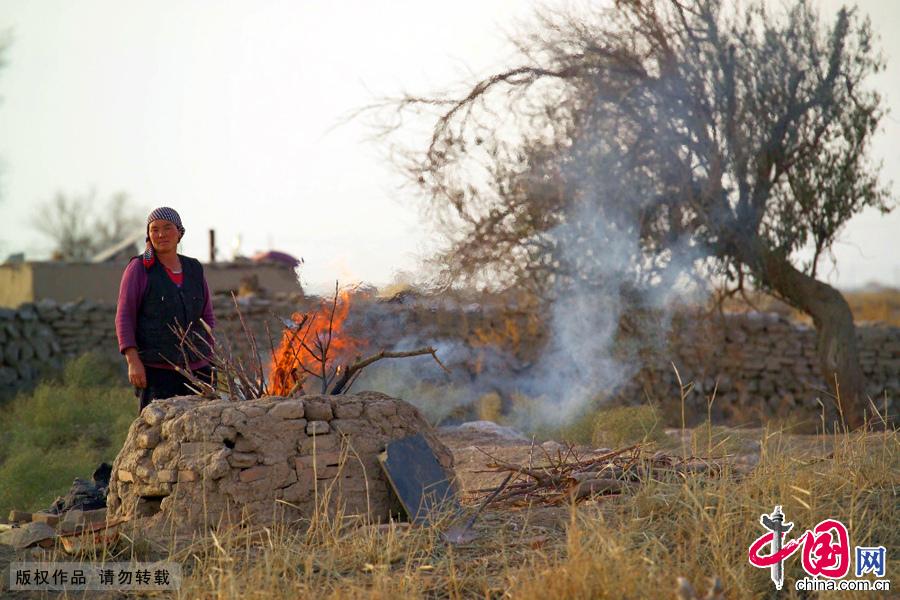 戈壁烤馕前的准备,用干柴把馕坑烧热。