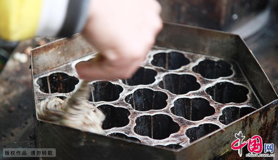 制作梅花糕有特殊的模具。厨师给梅花型模具上油,这样面浆就不会粘到模具上,也不会糊掉。中国网图片库 刘建华/摄