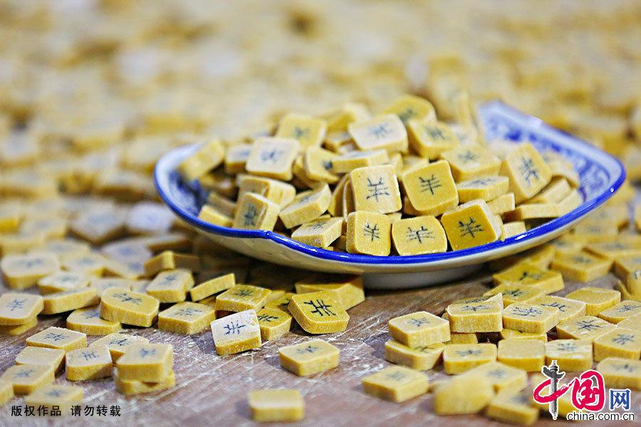 字豆糖由麦芽糖稀、黑芝麻粉、黄豆粉三种原生态的材料组成,经过制糖艺人巧妙制作,在切开的每块糖片中,都会蕴藏着一个吉祥如意的汉字,是一种可食可赏的民间糕点。中国网图片库 施亚磊/摄