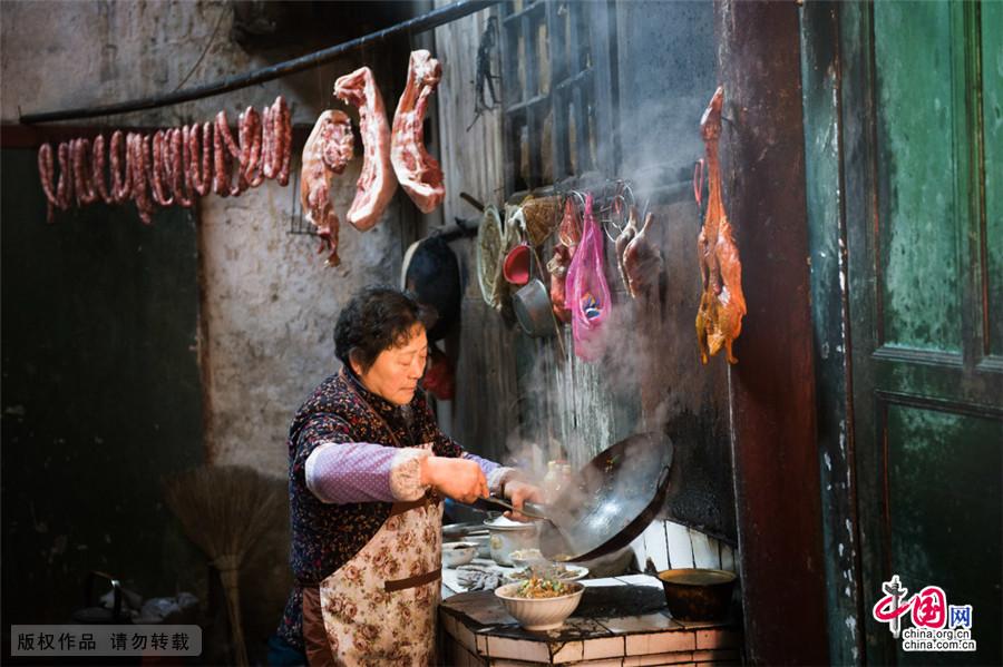 古城里,几乎家家户户厨房里灶台前都挂满了这样的年货,不但有猪肉,还有板鸭子和干仔鸡,灶台的烟火慢慢的熏烤。中国网图片库 尹忠/摄