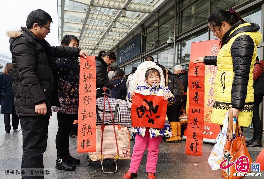 2015年2月4日,為期40天的2015年春運大幕正式開啟。當日也恰逢立春時節,上海鐵路局文聯的藝術家們在鐵路上海站南廣場,為即將踏上返鄉旅途的旅客們現場免費書寫春聯,送上新春祝福。圖為旅客拿到春聯在晾幹墨跡。中國網圖片庫 賴鑫琳/攝