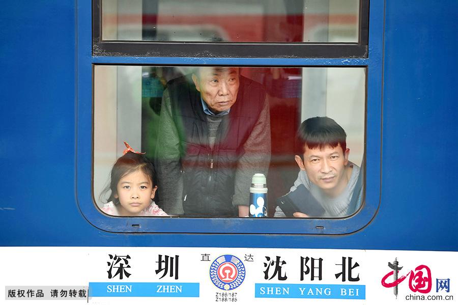 2月7日,在安徽亳州火車站開往深圳的列車上,乘客向車窗外張望。中國網圖片庫 劉勤利/攝