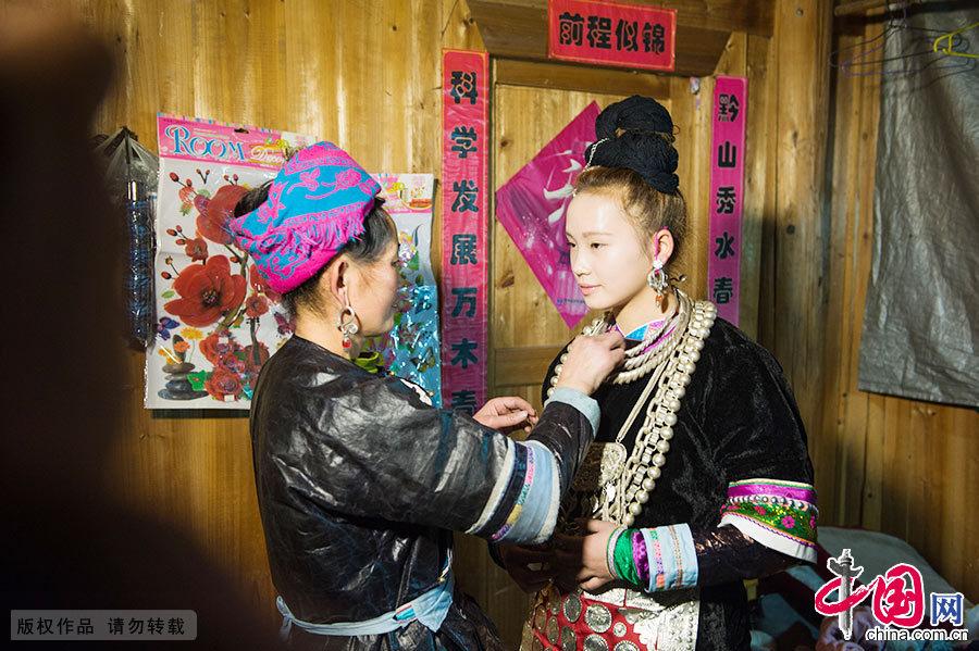 早上,妈妈给新娘潘妹花精心打扮,穿上了传统的嫁妆。中国网图片库 尹忠/摄