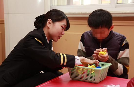 志愿者们在为自闭症儿童做康复训练(中国网