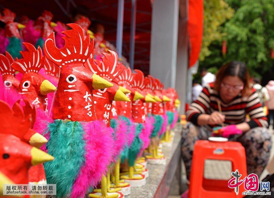 """南海神庙的庙会是一种古老的汉族民俗及民间宗教文化活动。在每年农历二月十一至十三举行,其中十三为正诞,也叫菠萝诞。""""波罗诞""""买菠萝鸡是自古流传下来的习俗之一,图为商家在现场制作民俗工艺品菠萝鸡。中国网图片库 许建梅/摄"""