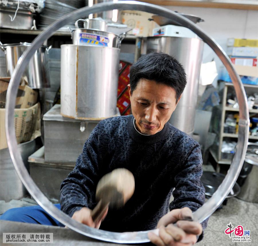 4月9日,江西省德兴市泗洲镇民间铁皮工匠汪光耀正在用铁皮为客户制作生活器具。中国网图片库 卓忠伟/摄