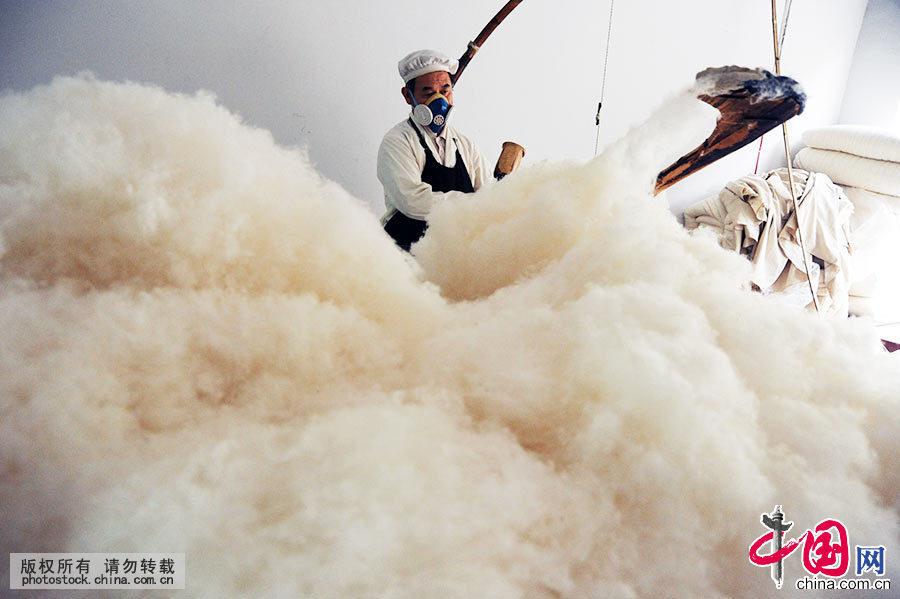 弹花匠,又名弹花工,一种以加工棉被为主的职业,在三百六十行中排名靠前,是一种非常古老、具有浓郁传统文化的手工工艺。图为民间艺人王定民在打花,为居民加工棉被。如今,手工弹花已淡出普通人记忆。中国网图片库 饶国君/摄
