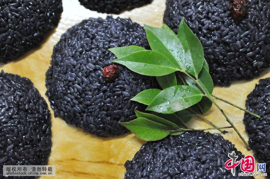 """乌米饭也叫糯米饭,分甜、咸两种。是用一种名叫""""乌饭叶""""的野生灌木叶子,经过清洗搓叶、沥汁、糯米浸泡、上笼蒸熟做成的。中国网图片库 胡剑欢/摄"""
