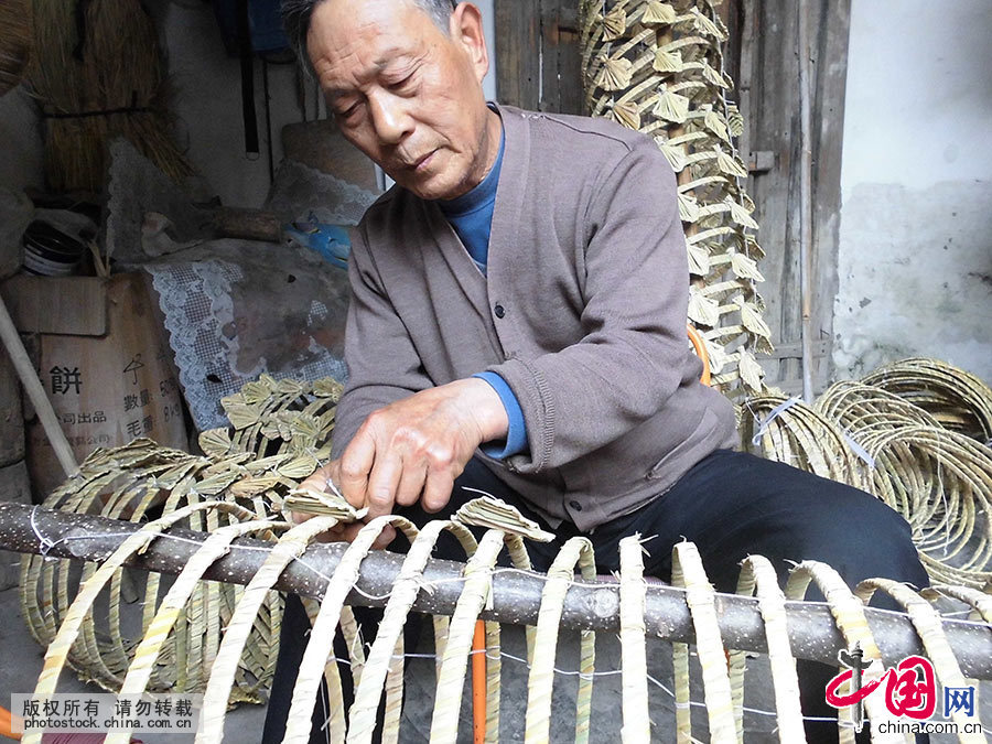 编扎湖口草龙的第三代传承人喻芳泽在龙骨架上安装龙片。中国网图片库 洪永林/摄