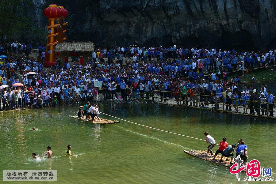 """图为人们观看广西乐业县壮族卜隆古歌节""""水上拔河""""比赛。中国网图片库 韦万忠/摄"""