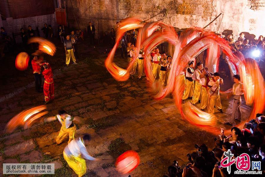 雪峰断颈龙灯,传说是古乡民为纪念被唐朝宰相魏征误斩的泾河老龙王而兴起的民俗文化活动;一串龙灯有两个龙头,龙头和龙身是分开的,十三截龙身用白布相连,故称断颈龙灯。在舞动的时候,龙头追着龙珠四下盘旋,龙身上下翻滚,光影穿梭,颇为壮观。中国网图片库 尹忠/摄