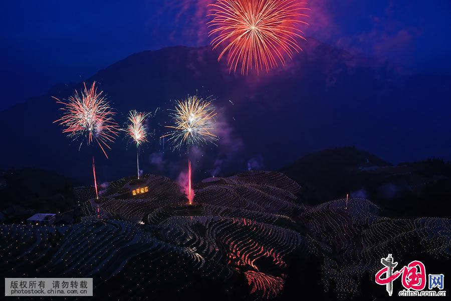 """入夜,平安壮寨村民在形如""""七星伴月""""的梯田上点燃万支火烛,呈现繁星闪烁的美丽壮锦。同时,燃放烟花,刹时,烟花腾空,五彩缤纷。 中国网图片库 肖远泮 摄"""