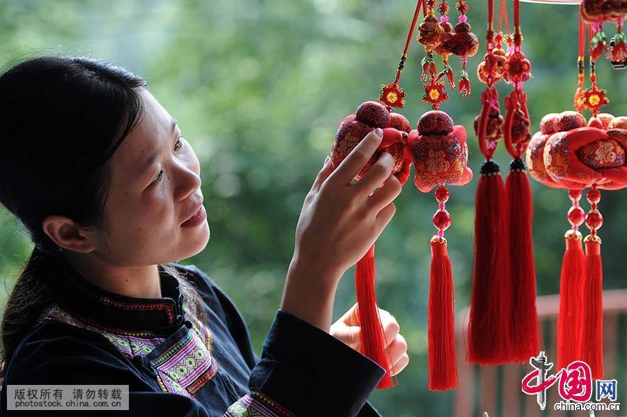 """""""麽乜""""是百色市右江上游地区壮族特有的民间吉祥饰物,是当地壮族民间传统工艺品之一 ,大小不一、五颜六色,其造型是勇士伸开四肢拥抱龙珠,寓意是守护太阳、拥抱希望。中国网图片库 韦万忠 摄"""