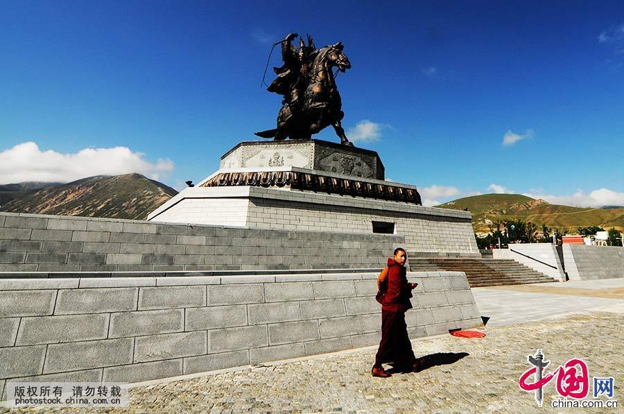 一名僧人走过玉树的地标式建筑格萨尔王塑像前。
