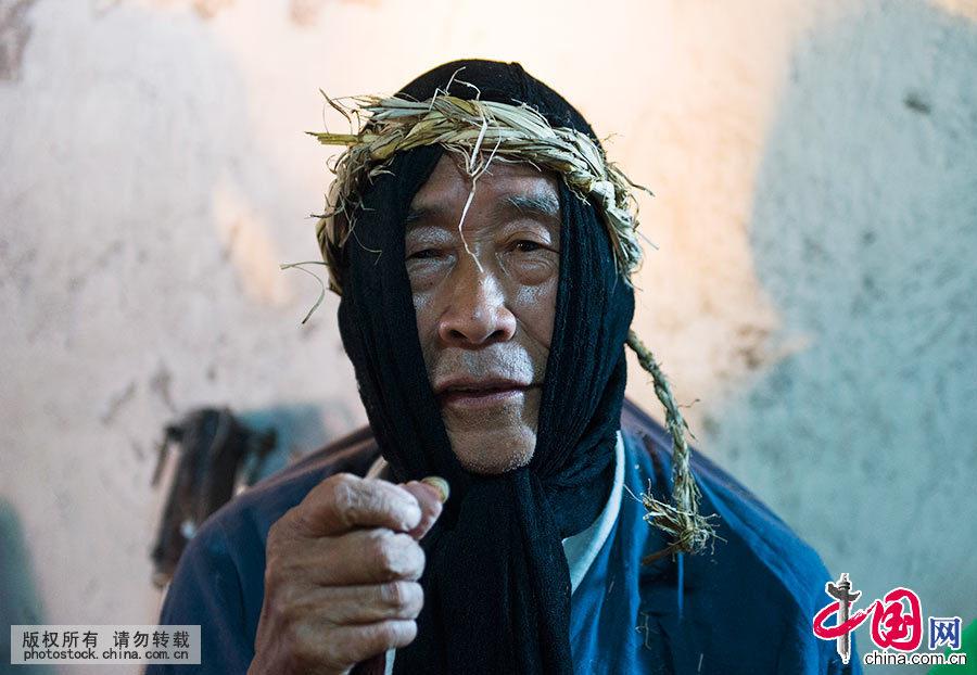 """楊國順,是會同高椅儺戲目前的傳承人。演出前的化粧比較簡單,不用塗脂抹粉,穿上服裝,帶上儺面具即可。楊國順説:""""不戴面具是人,戴上面具是神。""""中國網圖片庫 尹忠 攝"""