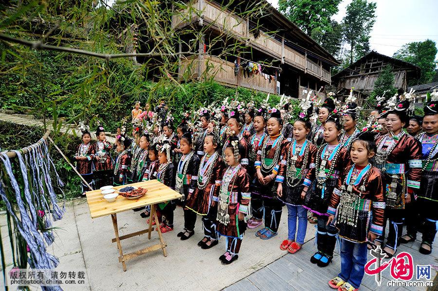 侗民族的人生就是歌唱的人生,歌、唱歌与他们的日常生活有着千丝万缕的联系。远方客人即将进寨,侗家人在寨门口摆下拦路酒,孩童们用稚嫩清脆的歌声热情迎接客人的到来。中国网图片库 杨希 摄