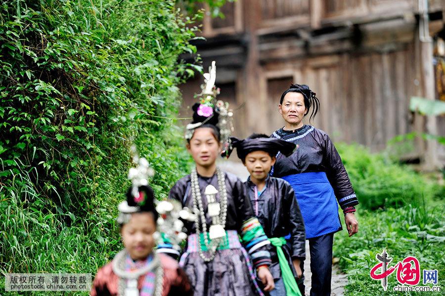 胡官美带着孩子走山路去学校。当地小学开始实施侗族大歌进课堂,组建校园侗歌队,聘请她一周两次进校传歌。中国网图片库 杨希 摄