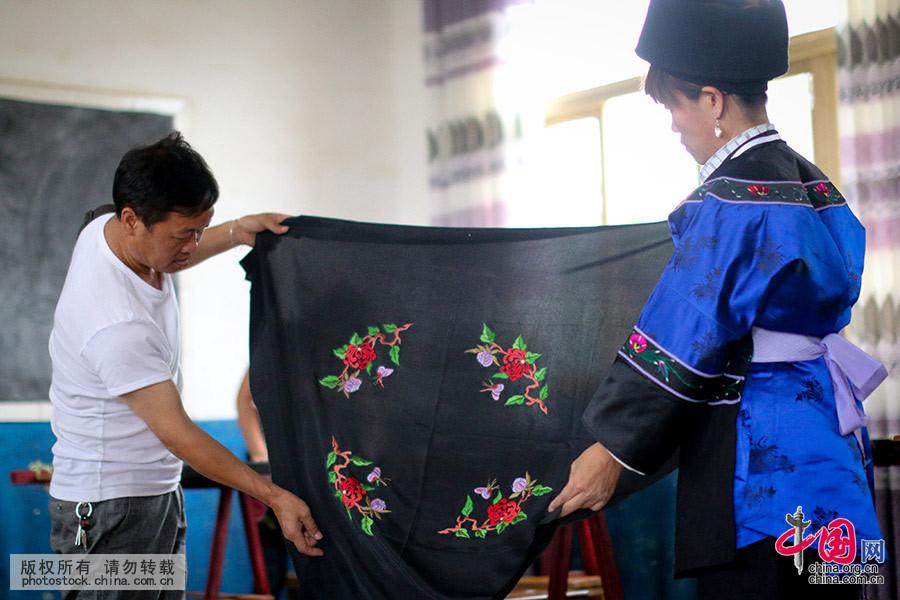 """布依汉子周后国(左一)这位刺绣传人说:""""要做布依族文化的推广者,打工赚钱的事情就让年轻人去干吧,我要留在寨子里把这件大事情做好,这是一件对得起祖先、对得起子孙的大事情啊""""。中国网图片库 张晖 摄"""