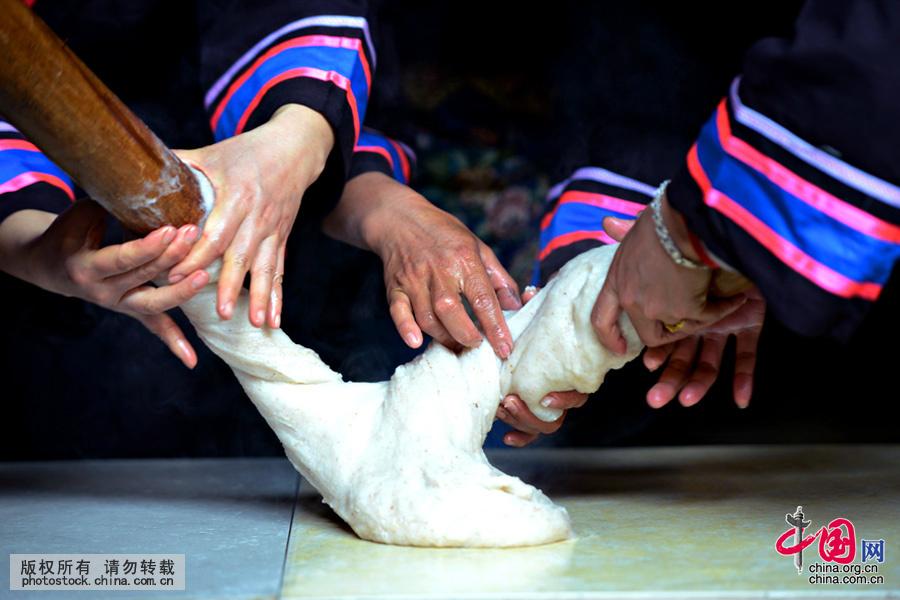 把舂好的糯米团放置在事先洗干净并涂上蜂蜡或茶油的桌板上,眼疾手巧的壮家妇女们就开始大显身手了。中国网图片库 黄旭胡摄